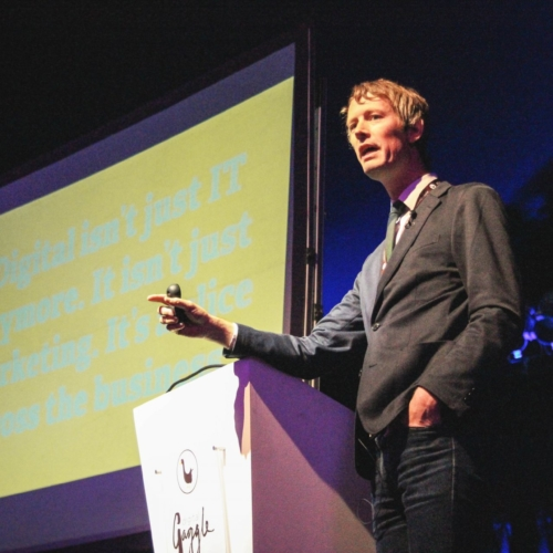 James Caig on stage speaking at Digital Gaggle