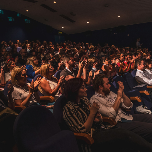 Inside the cinema, attendees clapping