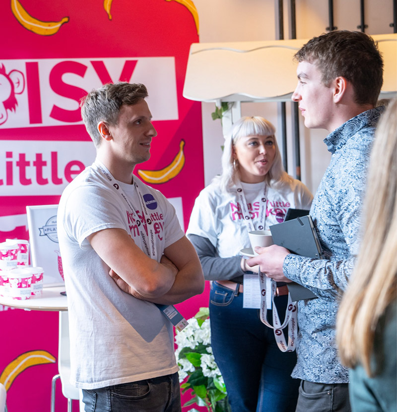 Team members from Noisy Little Monkey talking to attendees at their stand